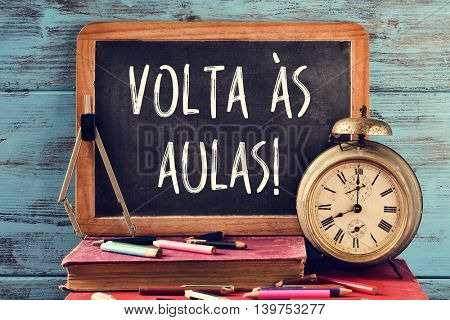 a chalkboard with the text volta as aulas, back to school in portuguese, some old books, an old clock, a compass and some pencil crayons of different colors, against a blue wooden background