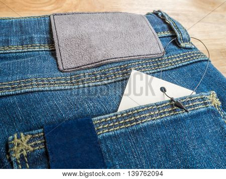 Close-up of blue jeans with deerskin label and white blank price tag in pocket on wooden texture background