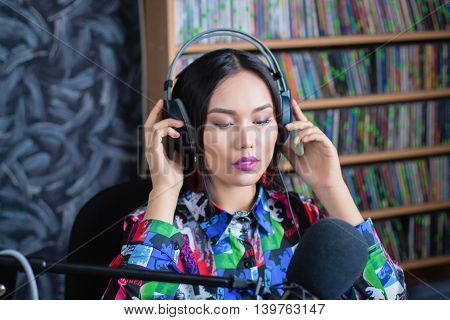Beautiful girl in headphones with a microphone on the radio in the studio