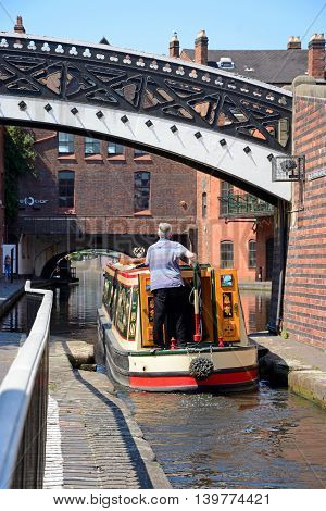 BIRMINGHAM, UNITED KINGDOM - JUNE 6, 2016 - Man steering a narrowboat under a footbridge at Gas Street Basin Birmingham England UK Western Europe, June 6, 2016.