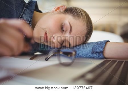 Young tired businesswoman taking nap on desk in creative office