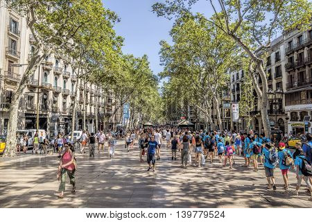 BARCELONA SPAIN - JULY 5 2016: Hundreds of people promenading in the busiest street of Barcelona the Ramblas.