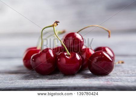 Dark red cherries. Cherries on gray wooden surface. Juicy berries from the garden. Fruit of summer.