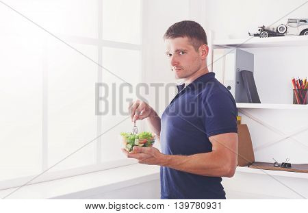 Man has healthy business lunch in modern office interior. Young handsome businessman profile portrait near window with vegetable salad in bowl, diet and eating right concept. High key image