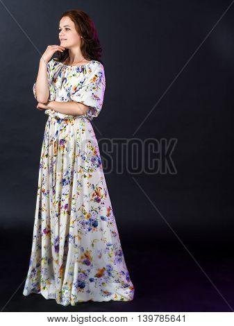 Beautiful Russian woman in long summer dress in a rustic style