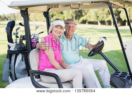 Portrait of cheerful mature couple sitting in golf buggy