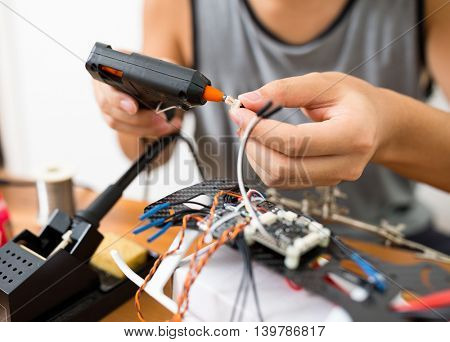 Man using hot glue to stick component together