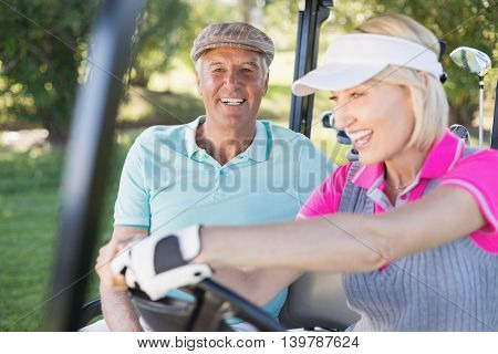 Smiling mature couple enjoying in golf buggy