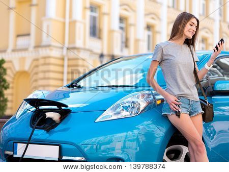 Lets look here. Lovely calm woman looking at her smartphone while charging her hybrid car in the city