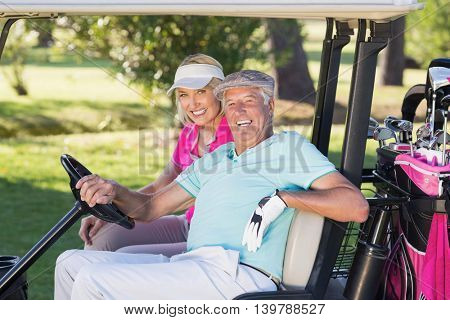 Portrait of cheerful mature golfer couple sitting in golf buggy