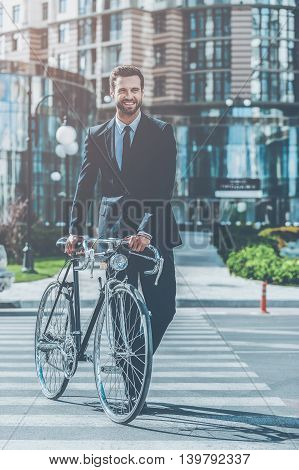 Green way to get to work. Full length of smiling young businessman rolling his bicycle while crossing the street