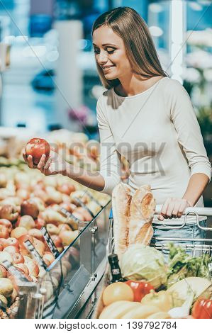 Selecting the freshest products. Beautiful young woman holding apple and smiling while standing in a food store