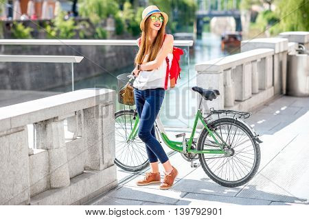 Young female traveler standing with bicycle on the street near the river in Ljubljana city. Traveling in Slovenia