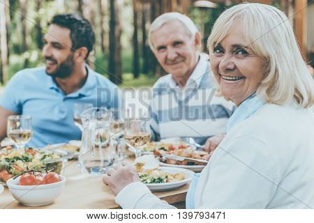 Proud of her big family. Happy family sitting at the dining table outdoors while senior woman looking over shoulder and smiling