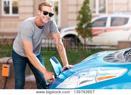 Lets do it. Elated young man looking at the camera while plugging his electric car to electricity in the city