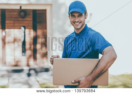 Happy delivery man. Cheerful young delivery man holding a cardboard box while standing against residential house