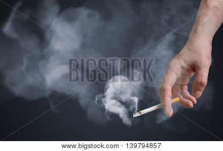 Smoker is holding smoking cigarette in hand. A lot of smoke around.