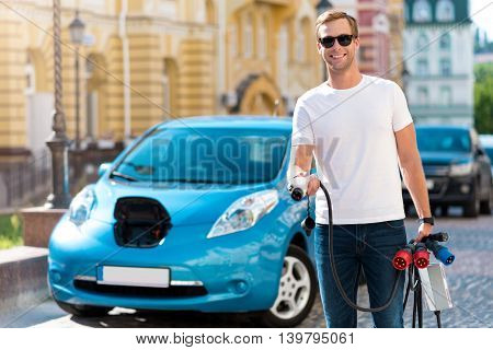 Have a look here. Joyful sincere man holding a lot of power cables to the electric vehicle in front of one