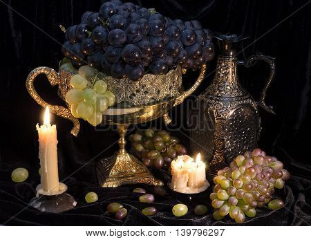 Still life with grape, decorated ware and candles