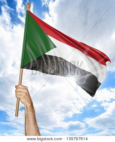 Person's hand holding the Sudanese national flag and waving it in the sky, 3D rendering