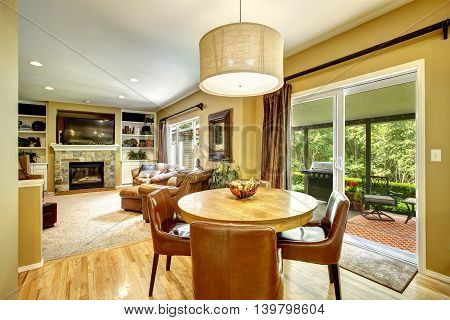 Living room interior with round dining table and leather chairs view of walkout deck poster