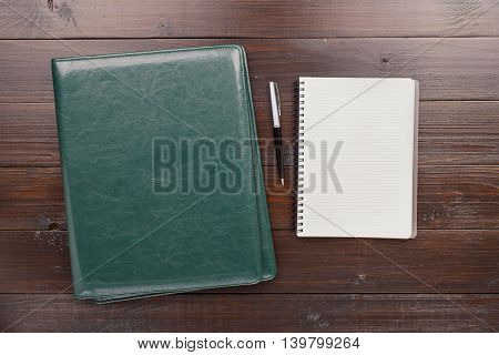 On the Office Desk Is Open Notebook With Blank Pages Pen And Leather Business Folder. Top view. Business Background
