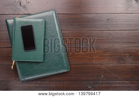 Smartphone With Blank Screen And Green Leather Business Folders. Top View With Copy Space