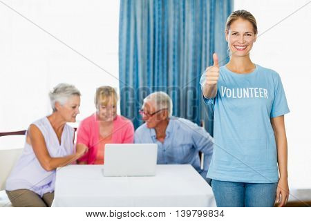 Volunteer with thumbs up in a retirement home