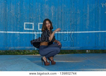 Young sexy suntanned woman in a short top shirt and leggins on high heels with beautiful modern make-up and hair dancing against blue painted wooden wall with copy space horizontal view