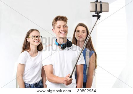 A group of friends taking a picture selfie phone placed on a monopod