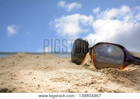 sun glasses in beach sand against the blue sky with clouds concept of summer vacation copy space selected focus very narrow depth of field
