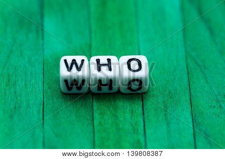 Who Cube Blocks Arranged On Green Wooden Background