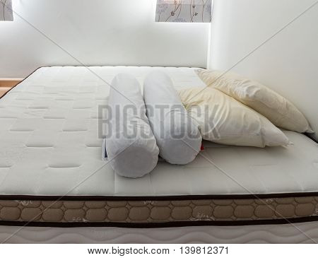 White bolster and dirty pillow on the clean bed in the bedroom.