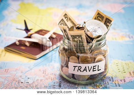 Travel budget concept. Travel money savings in a glass jar with compass passport and aircraft toy on world map poster