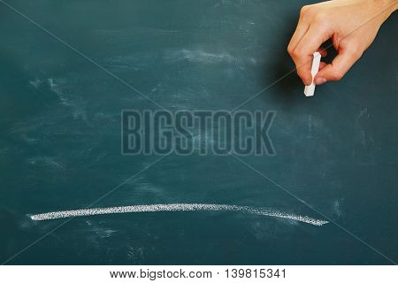 Hand with chalk drawing a white line stroke on a green chalkboard