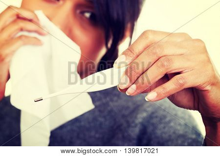 Young sick woman checking her temperature