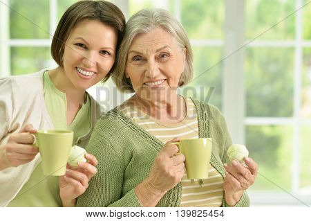 Portrait of Senior woman with daughter with tea at home