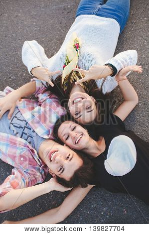 Three happy teenage friends lying together and laughing. Top view. Best friends.