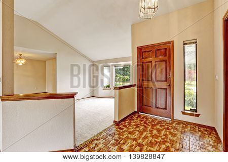 View Of Entryway With Brown Tile Floor And Vaulted Ceiling.