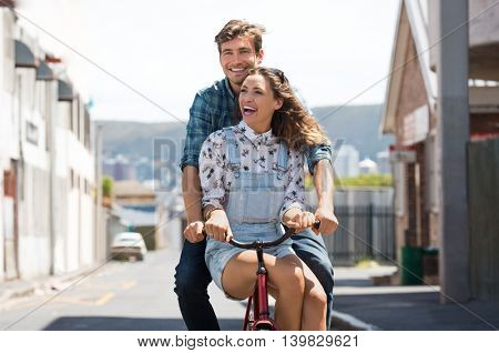 Happy young couple riding on a bicycle together. Beautiful happy girl sitting on a bike tube while her boyfriend riding a bike on the street. Laughing young man and young woman having fun on bike.