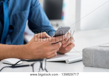Close up hands of businessman using mobile phone. Closeup of a businessman hand holding smartphone and messaging. Detail of businessman checking email with cellphone.
