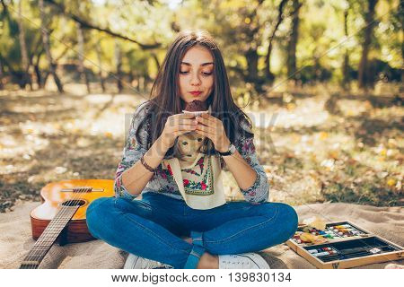 Cute teenage girl hipster looking at brownie cupcake outside on autumn day. Artsy young woman with guitar having a picninc in forest