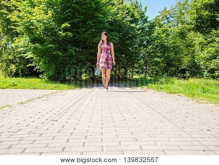 young pretty woman goes barefoot on the sidewalk and holding a shoe on sunny summer day
