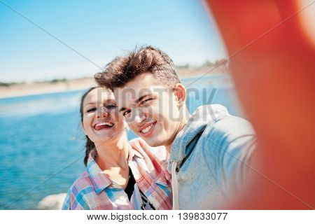 Young couple making a selfie outdoors and playing ape. Teenage girl and young man having fun with camera on a sunny day