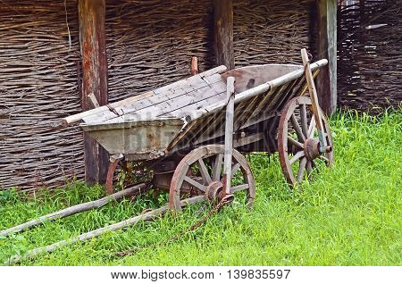 Ancient wooden cart standing on a green grass