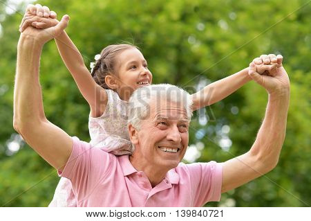 Happy elderly man with granddaughter in spring park