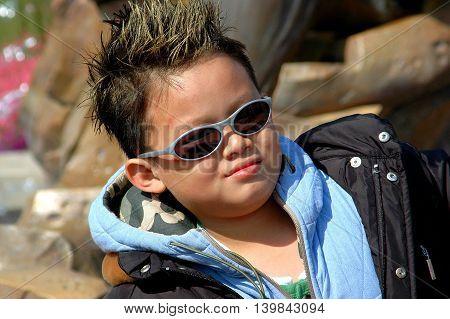 Hong Kong China - December 13 2006: Hip Chinese boy sporting shades and a trendy frosted haircut at Disneyland