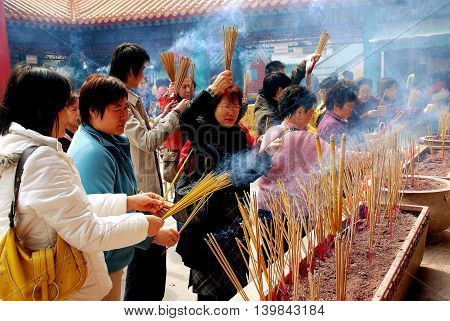 Hong Kong China - January 23 2007: Devout Buddhist Chinesewith incense sticks pray at the Wong Tai Sin temple in Kowloon