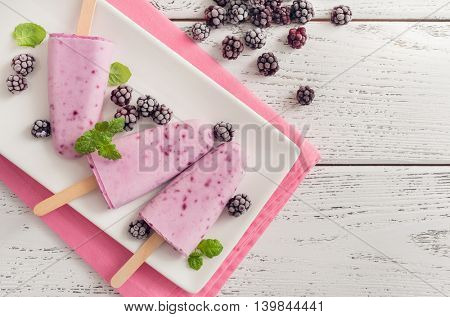 Blackberry popsicle with berries on wooden background, popsicle top view