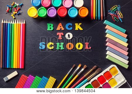 Colored letters frame laid out in the center of the phrase Back to school Various tools for painting and art in graphite black background. Accessories for drawing.